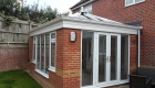 Red brick orangery with white windows and doors