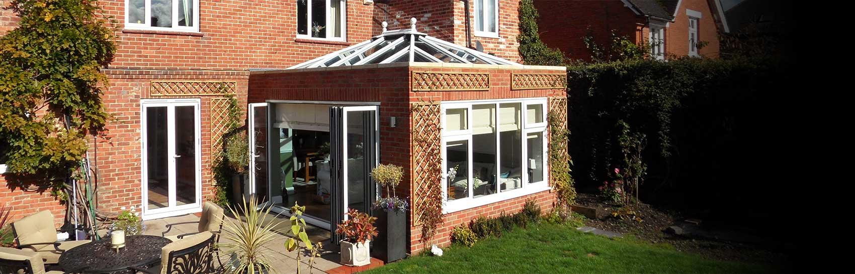 A luxury orangery installation leading onto patio and garden