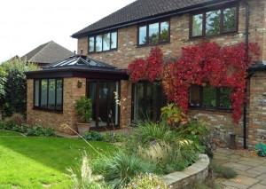 Mahogany coloured orangery that matches the windows and doors of the property