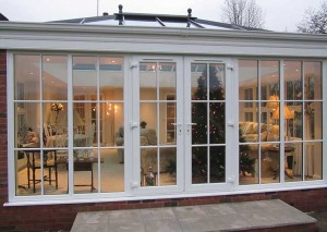 An orangery with windows and doors that have georgian bars