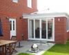 Red brick orangery that opens out onto a stylish patio