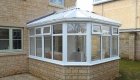 A white victorian conservatory with light stone base